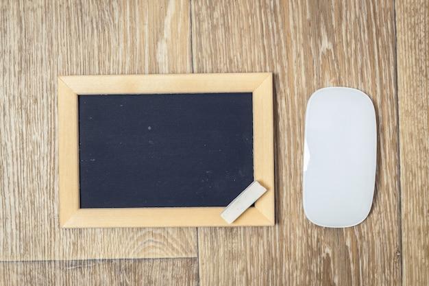 Mały blackboard na starym drewno stole z kredą