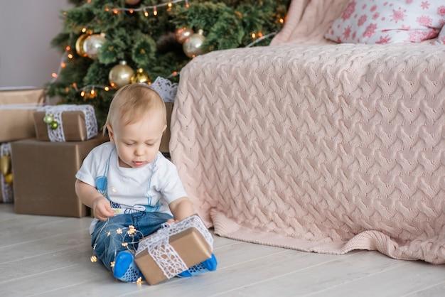 Mały blond chłopiec bawi się jasną girlandą na choince w przytulnym domu.