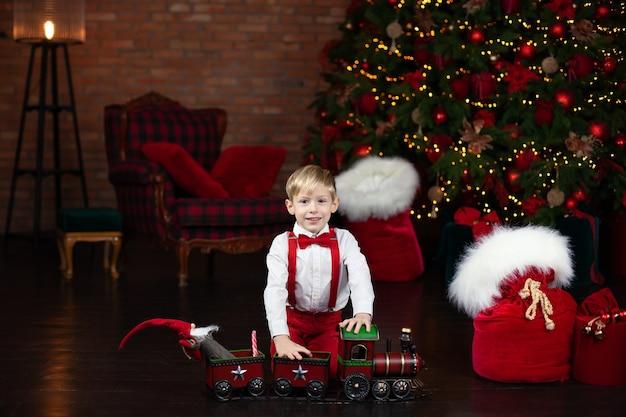 Mały blond chłopiec bawi się zabawkowym pociągiem parowym w domu