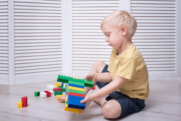 Mały blond chłopiec buduje kolorowy projektant