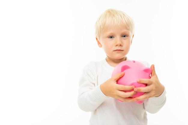 Mały blond chłopiec kaukaski z skarbonka różowy świnia na białym tle.