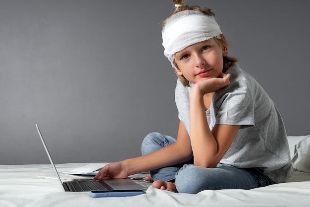 Mały blond chłopiec kaukaski z urazem głowy i bandażem siedzi na łóżku i używa laptopa