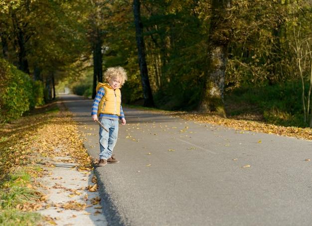 Mały blond chłopiec na poboczu małej drogi,