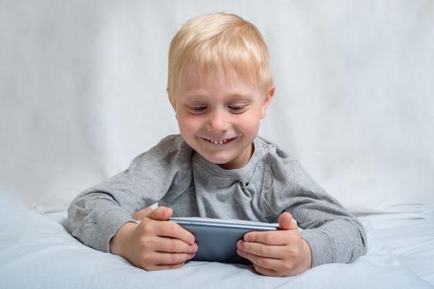 Mały blond chłopiec ogląda coś na smartfonie, leżąc w łóżku. gadżet wypoczynek