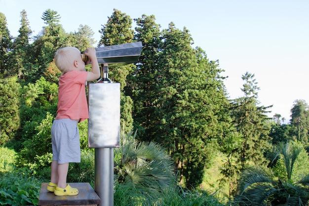 Mały blond chłopiec patrząc w dużej lornetce
