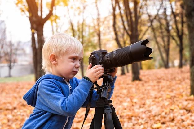 Mały blond chłopiec robi zdjęcia lustrzanką. jesienny park