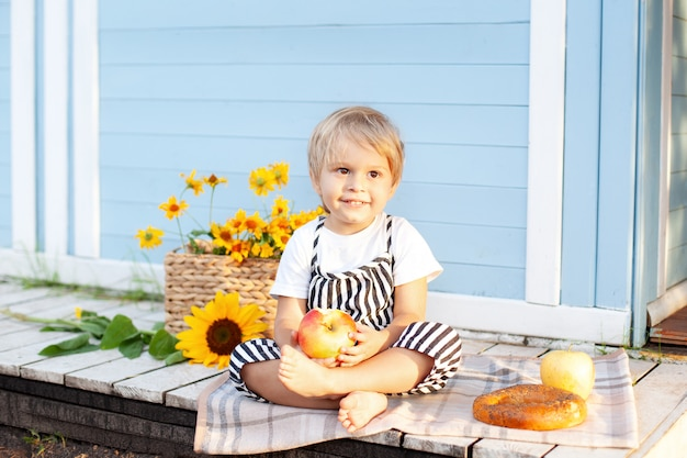 Mały blond chłopiec siedzi na drewnianym ganku w domu i je jabłko w jesienny dzień. koncepcja dzieciństwa. dziecko bawi się na podwórku jesienią. szczęśliwe dziecko. żniwny. mały rolnik. owoce i dziecko