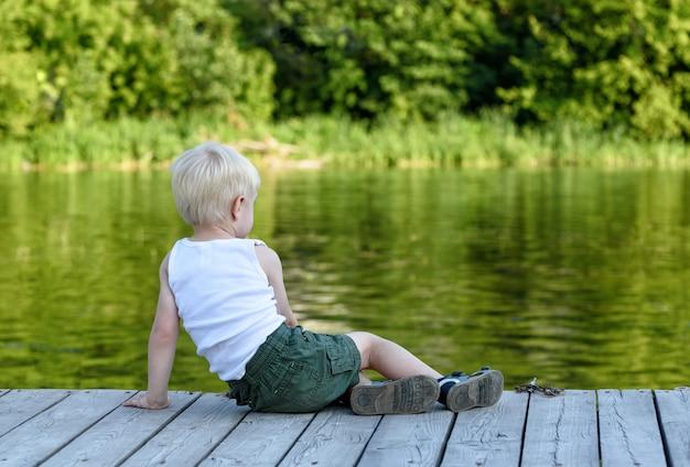 Mały blond chłopiec siedzi na molo na brzegu rzeki