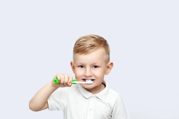 Mały blond chłopiec uczy się szczotkować zęby w domowej kąpieli