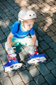 Mały blond chłopiec w białym sportowym kasku i niebieskiej koszulce jeździ na rolkach