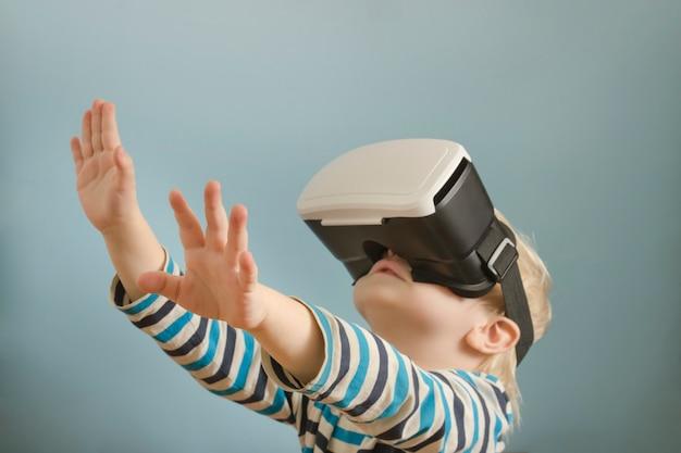 Mały blond chłopiec w okularach wirtualnej rzeczywistości.