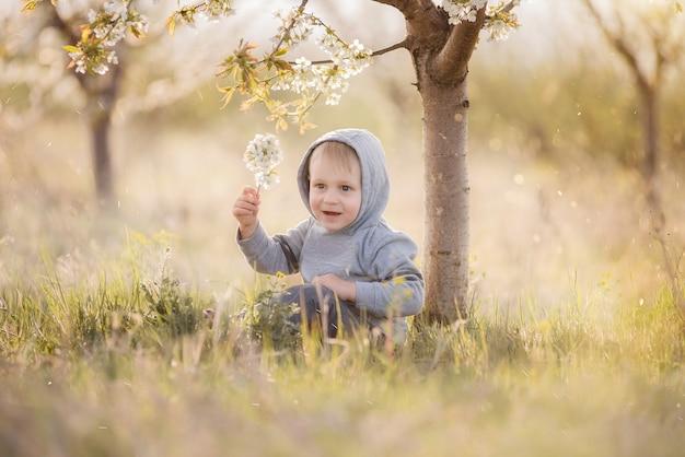 Mały blond chłopiec w szarej bluzie z kapturem na głowie siedzi w zielonej trawie pod kwitnącym drzewem