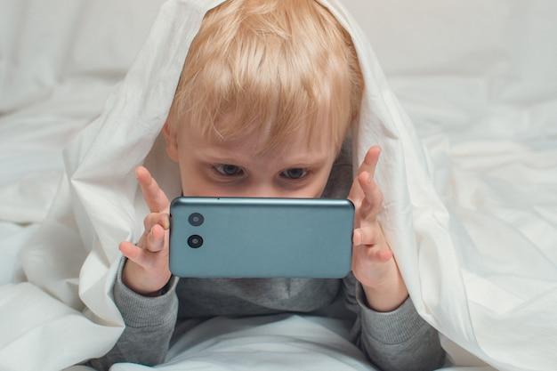Mały blond chłopiec zakopał nos w swoim smartfonie. leżąc w łóżku i chowając się pod kołdrą. gadżet wypoczynek