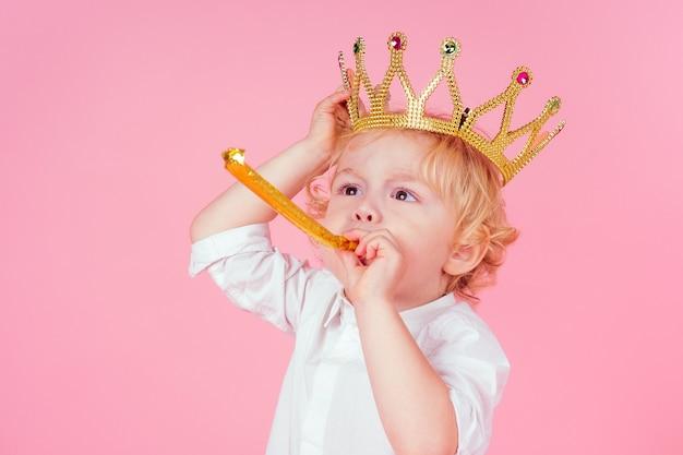 Mały blond chłopiec ze złotą koroną głowy loki fryzurę 4-5 lat w studio na różowym tle dmuchanie klaksonu gwizdek przyjęcie urodzinowe świętuje boże narodzenie i nowy rok król imprezy