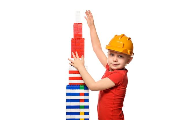 Mały blondyn w hełmie budowlanym i czerwonej koszuli stojący w pobliżu wieży zbudowany z części projektanta. portret. izoluj na białym tle.