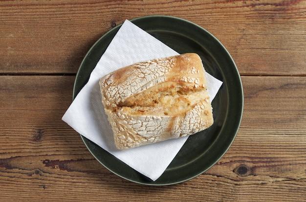 Mały bochenek chleba na talerzu na drewnianym stole