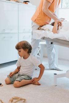 Mały braciszek bawi się na podłodze, podczas gdy lekarz pediatra i osteopata przeprowadza terapię fizjologiczną dla jego starszej siostry. czekające i znudzone dziecko w gabinecie lekarskim
