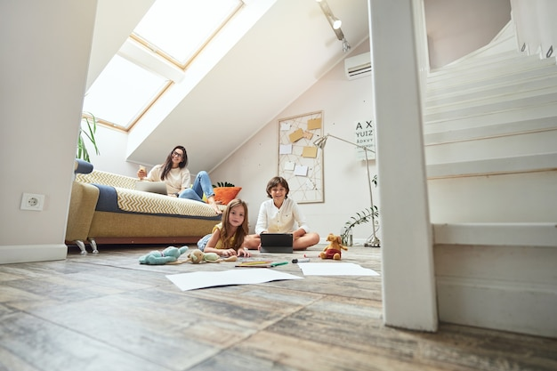 Mały brat i siostra siedzący na podłodze w salonie bawiący się lub odrabiający pracę domową