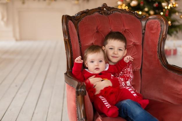 Mały brat przytula swoją młodszą siostrę w pobliżu choinki