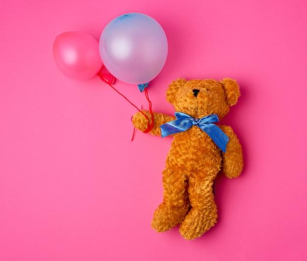 Mały brązowy miś trzyma dwa napompowane balony na linie