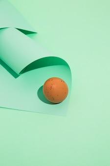 Mały brown kurczaka jajko z staczającym się papierem na zielonym stole