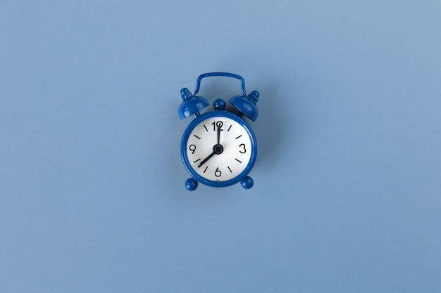 Mały budzik na pastelowym tle w klasycznym niebieskim kolorze, zbliżenie, widok z góry. minimalistyczny styl retro. zarządzanie czasem, koncepcja koloru roku 2020. skopiuj miejsce na tekst. orientacja pozioma