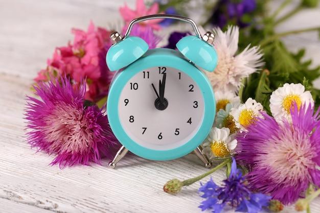Mały budzik z pięknymi kwiatami na stole z bliska