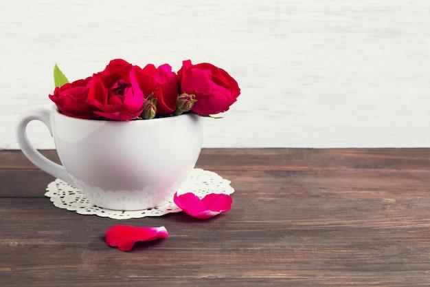 Mały bukiet czerwonych róż w białej filiżance na drewnianym stole i tle białej ściany
