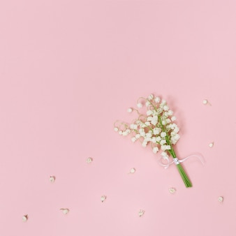 Mały bukiet konwalii na delikatnym różowym tle
