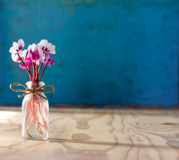 Mały bukiet kwiatów cyklamenu w szklanej butelce na drewnianym