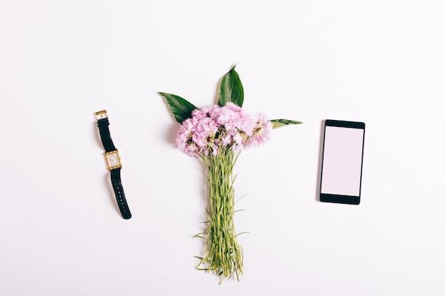 Mały bukiet różowych goździków, telefonu komórkowego i damskiego zegarka leżącego na białym stole