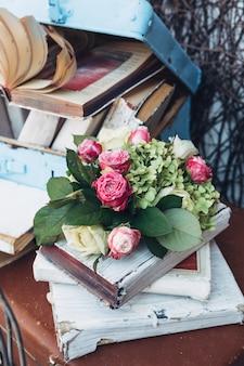 Mały bukiet różowych i zielonych kwiatów leży na starych książkach