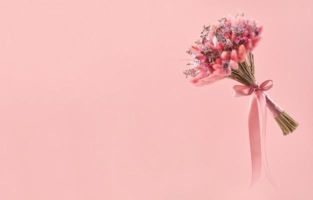 Mały bukiet różowych suszonych kwiatów z dzianiny z różową satynową tasiemką na różowym tle