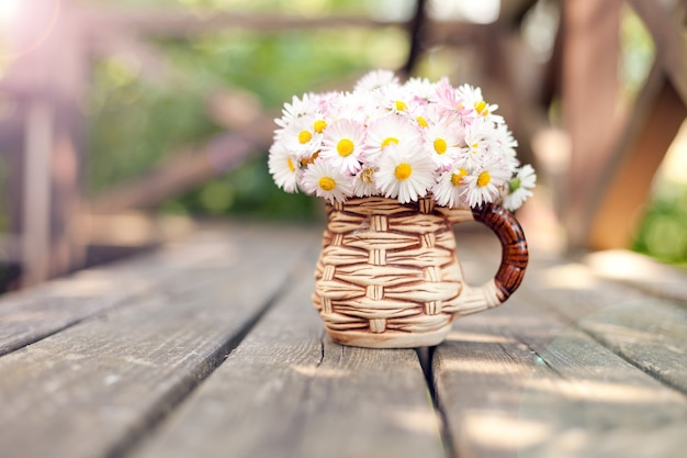Mały bukiet stokrotek w filiżance na grunge drewnianej desce na zielonym tle mały kwiatowy prezent dzień matki daisy bellis perennis kwiaty ogrodowe