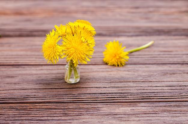 Mały bukiet żółtych kwiatów mniszek w wazonie na drewnianym tle. koncepcja sezonowości, wiosna. leżał z płaskim, miejsce na kopię, miejsce na tekst.