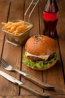 Mały burger wołowy z czerwoną cebulą, pomidorem, serem, majonezem, sałatą i frytkami