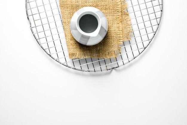 Mały ceramiczny czajniczek jest fotografowany na podstawie z płótna na siatce do suszenia ciasta