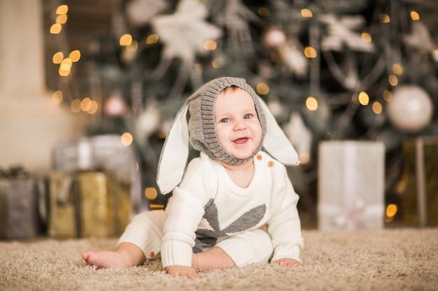 Mały chłopczyk pozowanie w białym pokoju z tłem bożego narodzenia