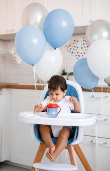 Mały chłopczyk siedzi w niebieskim krzesełku w domu na białej kuchni i wody pitnej z kubka niekapek na tle z balonami.