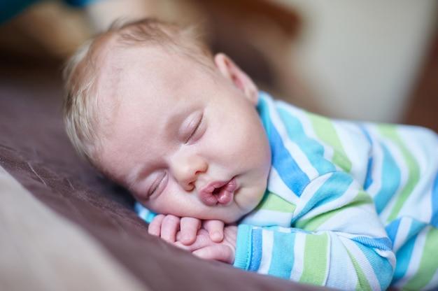 Mały chłopczyk śpi na brzuchu w łóżku
