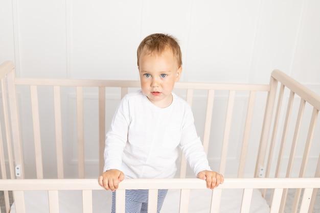 Mały chłopczyk w łóżeczku, patrząc w kamerę w jasnym pokoju dziecięcym