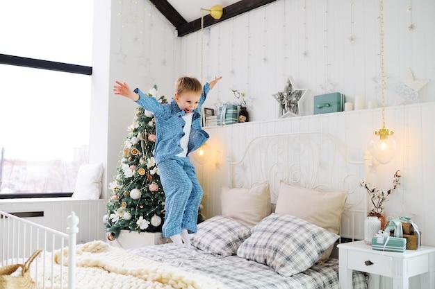 Mały chłopczyk w piżamie jest szczęśliwy i skacze na łóżku na tle choinki i prezentów. obchodzenie bożego narodzenia.