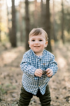 Mały chłopczyk w stylowej casualowej kraciastej koszuli i ciemnych spodniach, stojący w pięknym jesiennym lesie sosnowym, trzymając w rękach stożek i patrząc na aparat z uśmiechem