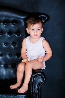 Mały chłopiec 2 lata w białej koszulce siedzącej na fotelu z czerwonym sercem balon