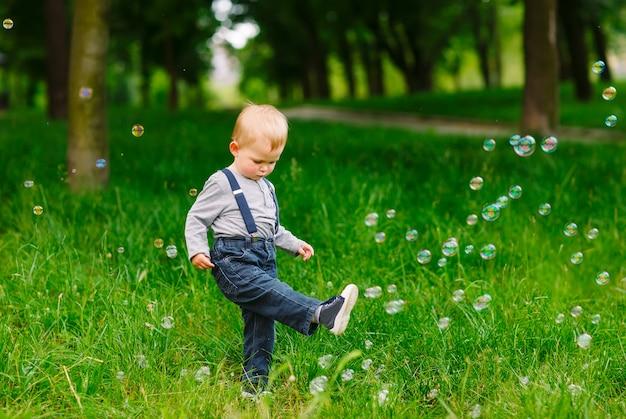 Mały chłopiec bawi się baniek mydlanych.
