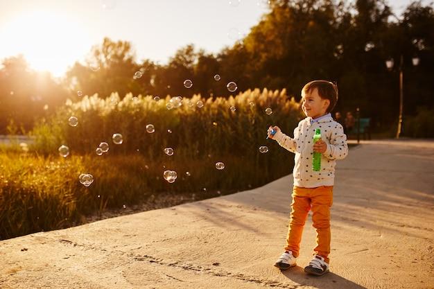 Mały chłopiec bawi się baniek mydlanych