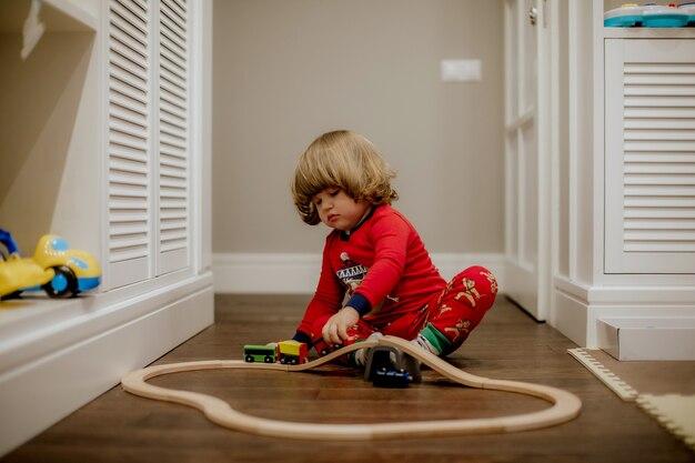 Mały chłopiec bawi się drewnianą kolejką na podłodze