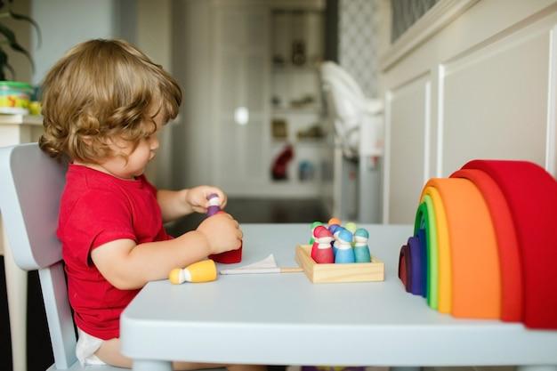 Mały chłopiec bawi się drewnianymi figurkami do zabawy przy stole