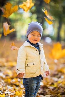 Mały chłopiec bawi się i podrzucając liście w jesień parku