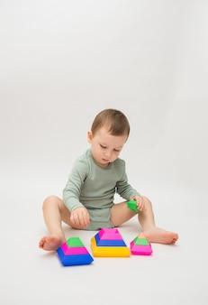 Mały chłopiec bawi się kolorową piramidą na białym tle z miejscem na tekst.
